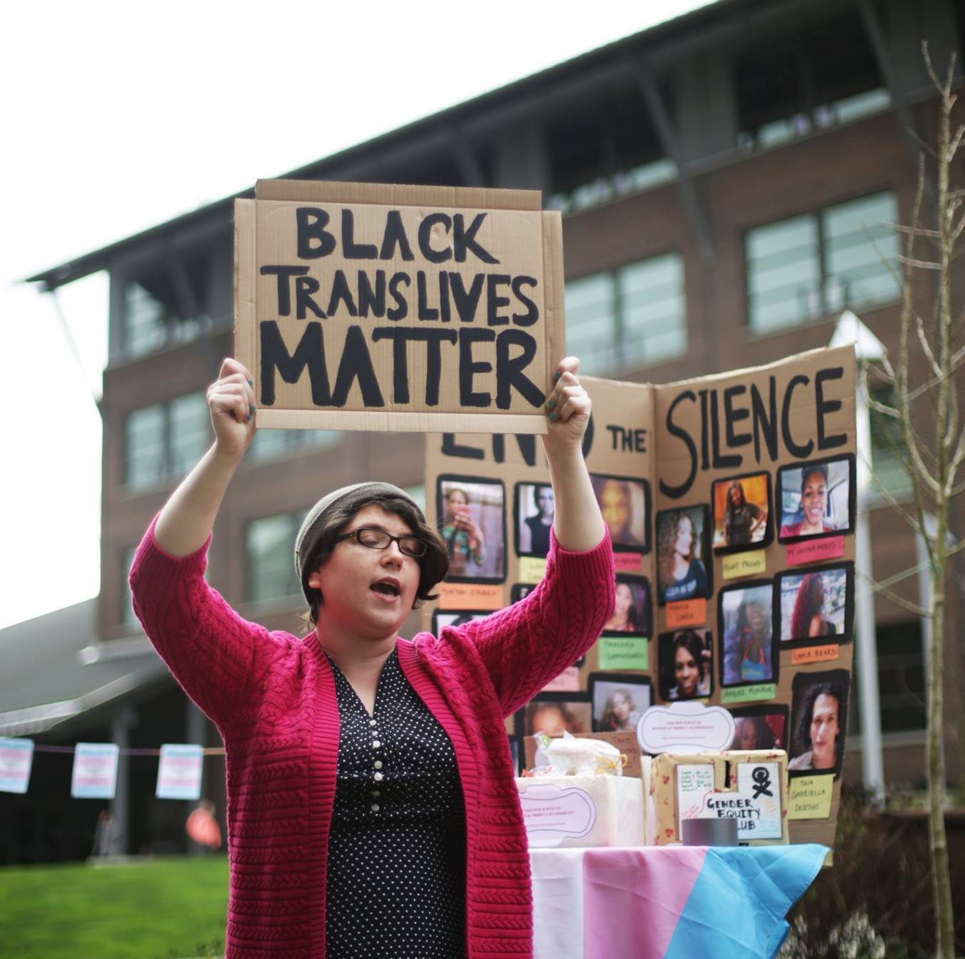 """A person holds up a sign saying """"Black trans lives matter"""""""